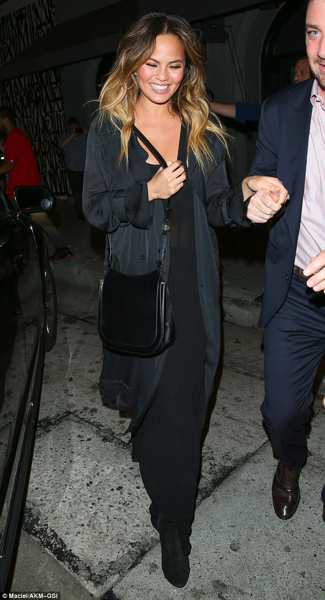Style savvy: Chrissy paired her flowing black maxidress with a chic silk jacket and leather satchel