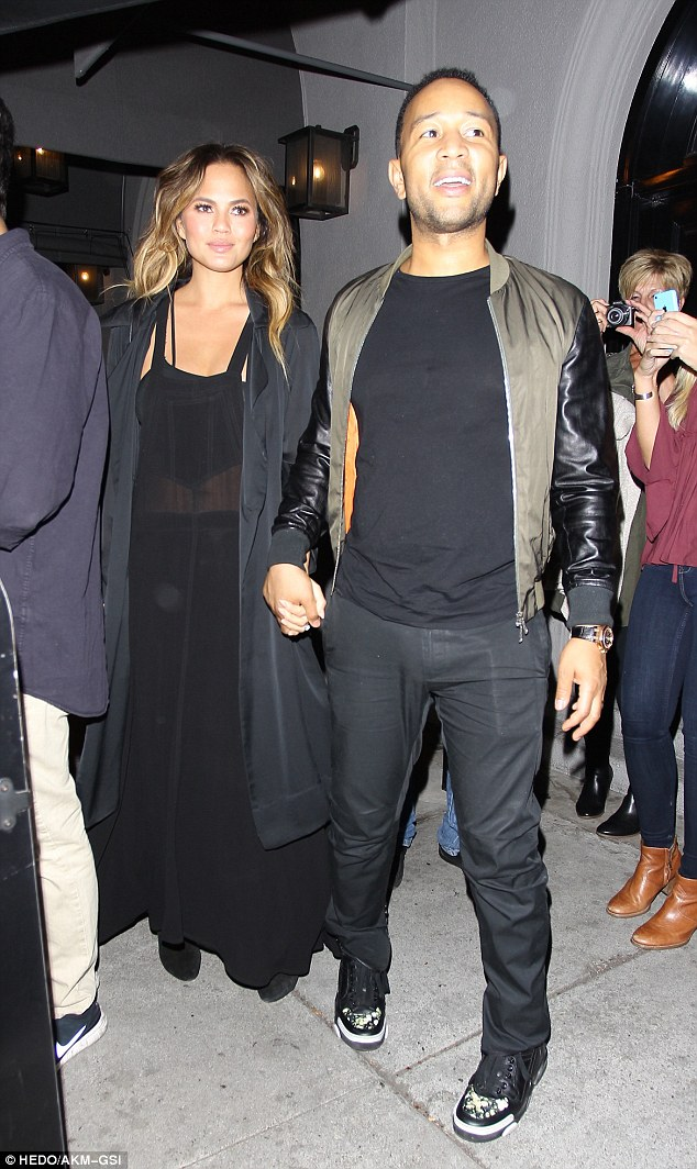 Cute couple: John led the way out of the restaurant, dressed down in a khaki bomber jacket with leather sleeves and black jeans