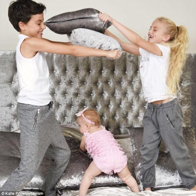 Family fun: A third image seesJunior, 10, and Princess Tiammii, eight, play fighting while the youngest member of the brood, Bunny, tries to join in