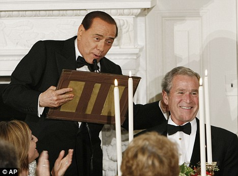 Whoops! Silvio Berlusconi pats George Bush as he hands him a piece of the podium he broke as he honoured the U.S. president at a White House dinner