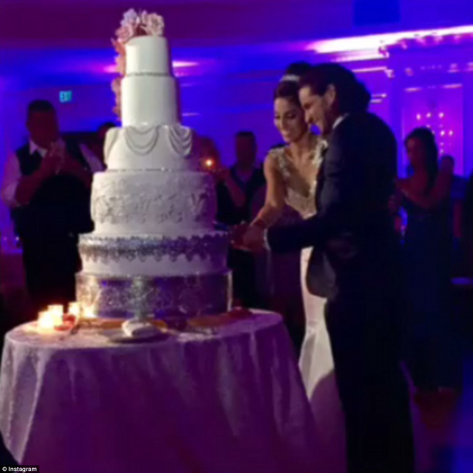They giggled together as they cut the enormous and extravagant cake during the wedding reception