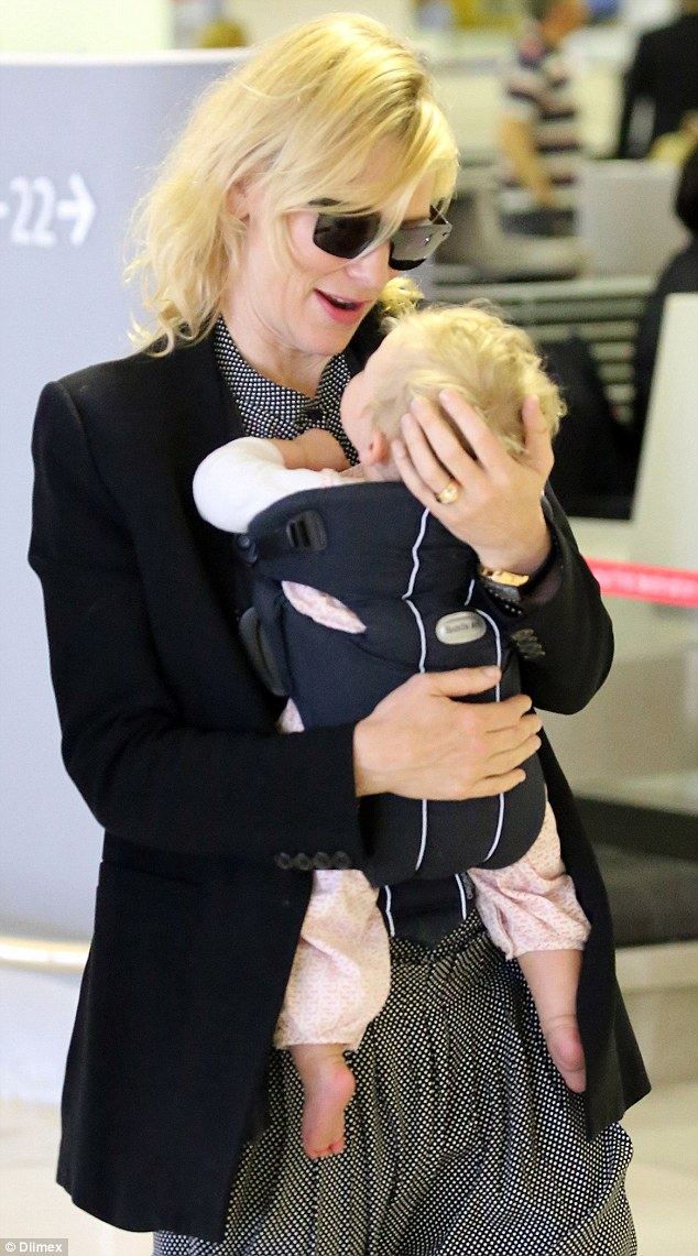 Airport attire: Cate wore a polished black blazer and black sunglasses while her daughter was dressed in a white tee and printed pants