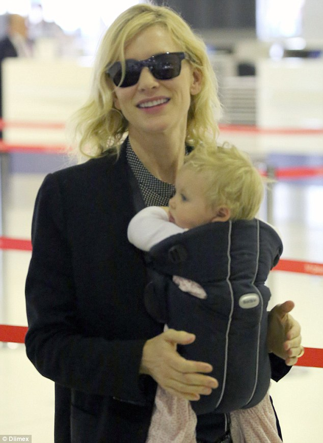 Maternal instinct: The 46-year-old mother looked smitten with her adorable  seven-month-old daughter as they made their way through the international terminal