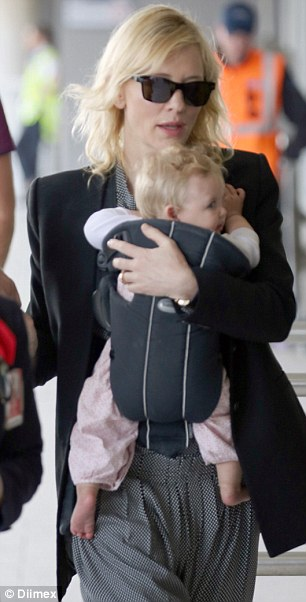 Baby grab: The chubby-cheeked adopted baby clutched at her Academy Award-winning mother from her carrier