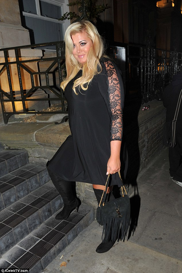 Glamorous: The 34-year-old wore a black mini dress which featured lace insets with a pair of thigh high boots