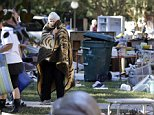 Rankin Craig watches as friends and family remove belongings from her flooded home in Forest Acres in Columbia, S.C., Wednesday, Oct. 7, 2015. People in the city are beginning cleanup after being pummeled by a historic rainstorm. (AP Photo/Chuck Burton)