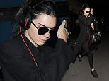 7 October 2015. Kendall Jenner appears rather camera shy as she arrives at Heathrow Airport on a flight from Paris Credit: Will/GoffPhotos.com   Ref: KGC-305
