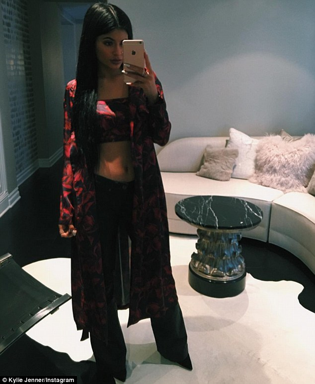 Fashionista: The meal saw Kylie flaunt her taut torso in a red and black printed bandeau crop top and a matching silk jacket