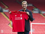 Liverpool's new manager Juergen Klopp poses for pictures in front of the Spion Kop stand after being appointed the club's new manager on a three-year deal, Liverpool, England, Friday, Oct. 9, 2015. The 48-year-old German has been out of work since May, when he ended a seven-year spell at Borussia Dortmund to take a sabbatical. (AP Photo/Jon Super)