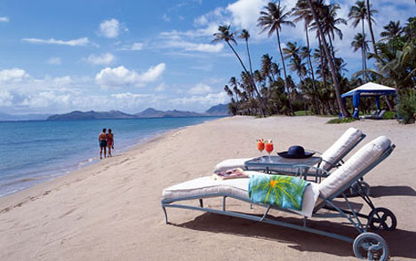 A view of a Caribbean beach with sunloungers and two people strolling along the sand