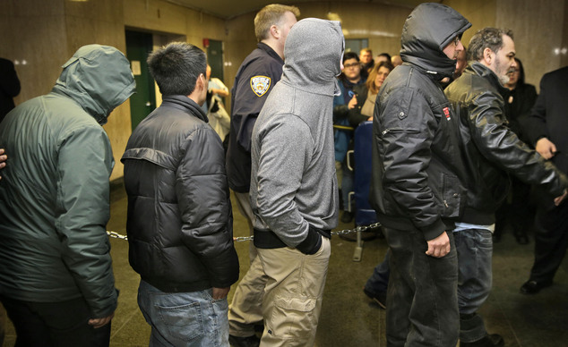 People chained together arrive for arraignment in a bribery scandal, Tuesday, Feb. 10, 2015, in New York. City inspectors, landlords and contractors formed a...