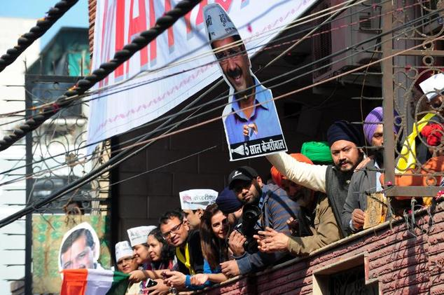 Indian supporters of the Aam Aadmi Party (AAP) wave a poster of Arvind Kejriwal as they celebrate his victory in state assembly elections in New Delhi, on Fe...