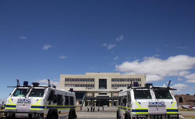 Police vehicles guard the parliament building in Lesotho's capital Maseru on October 17, 2014