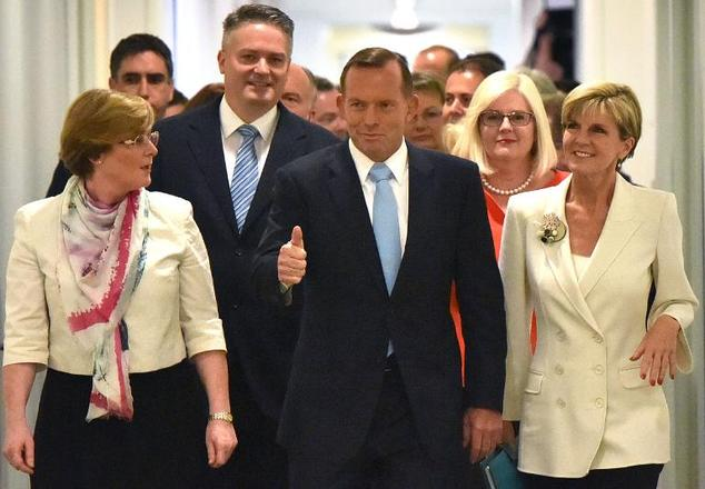 Australian Prime Minister Tony Abbott (C) walks with Foreign Minister Julie Bishop (R) to a coalition party room in Canberra on February 9, 2015 for a confid...