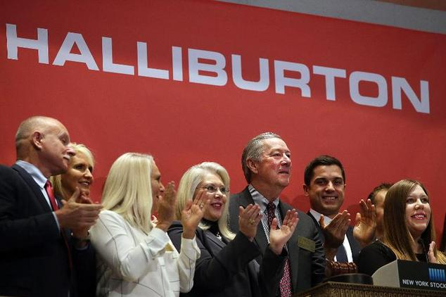 Halliburton, with CEO (3rd R) seen here at the New York Stock Exchange in New York City, Tuesday said it would cut up to eight percent of its global workforc...