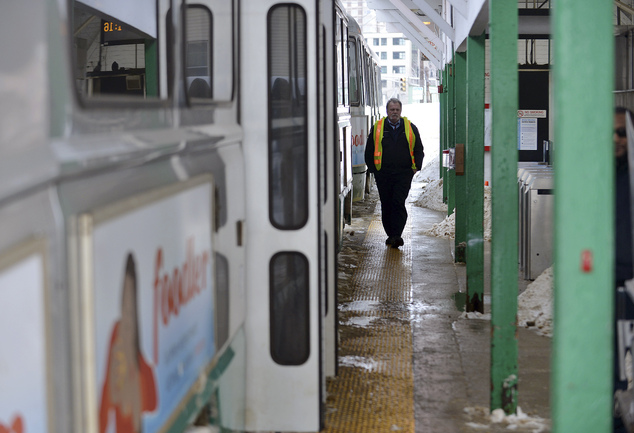 An MBTA Employee walks along the platform next to an idle transit train at the Leachmere T station in Cambridge, Mass., Tuesday, Feb. 10, 2015. The third maj...