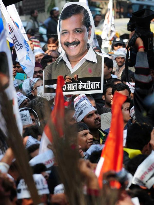 Indian supporters of the Aam Aadmi Party (AAP) wave brooms, the party symbol, and a poster bearing the image of party leader Arvind Kejriwal as they celebrat...