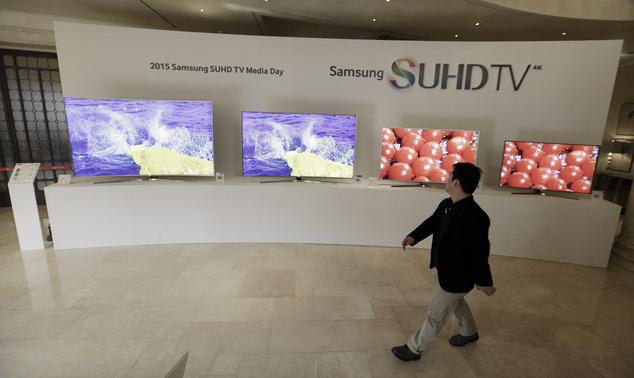 In this Jan. 5, 2015 photo, a journalist passes by Samsung Electronics Co.' SUHD 4K smart TVs on display outside the venue of a press conference in Seoul, So...
