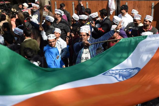 Indian supporters of the Aam Aadmi Party (AAP) wave brooms and a giant national flag as they celebrate their election victory in New Delhi, on February 10, 2015