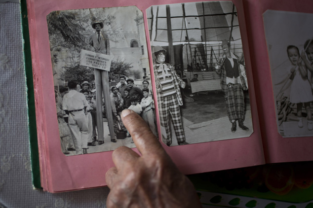 "In this Feb. 7, 2015 photo, veteran clown Ricardo Farfan, popularly known as ""Pitito,"" points to himself standing on stilts in a picture from the 1950's, dur..."