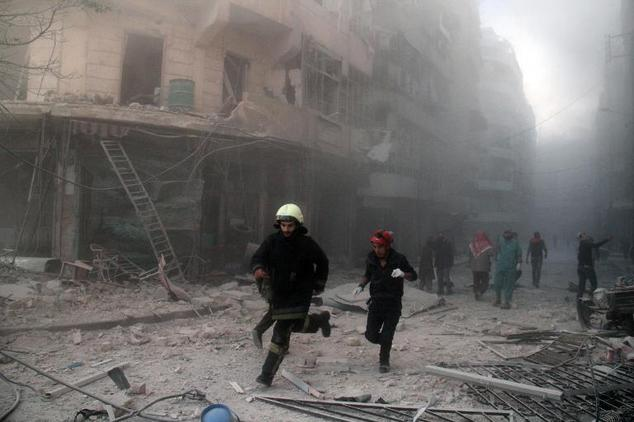 Emergency responders run after a reported barrel bomb attack by government forces in the Al-Muasalat area in the northern Syrian city of Aleppo, November 6, ...