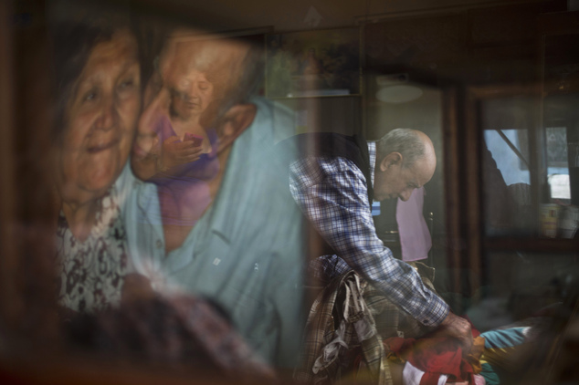 "In this Feb. 7, 2015 photo, veteran clown Ricardo Farfan, popularly known as ""Pitito,"" is reflected in a glass case as he prepares his clown costume for his ..."
