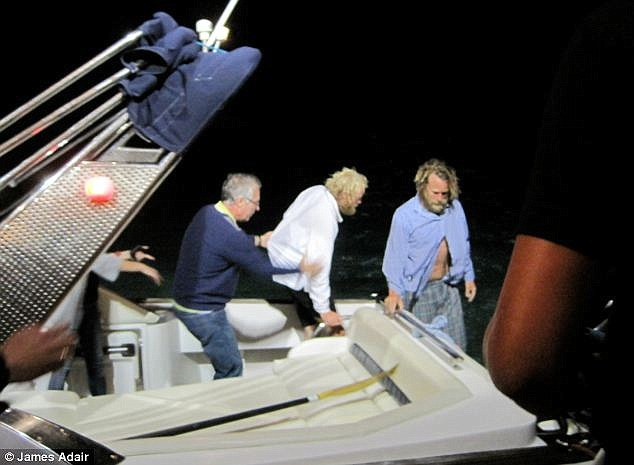 Success: The pair were thrown from their vessel into shark-infested waters after a large wave crashed into the boat, smashing it to pieces. However, after five hours in the sea, they managed to swim to a reef. Amazingly, they were later discovered by members of a local yacht club. Above, the men are brought back to land