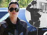 Khloe Kardashian wore an Adidas track suit to a Calabasas salon, with a bandana tied around her hair and a plaid button-up tied around her waist, otherwise dressed in shades of black, on Saturday, October 10, 2015 X17online.com