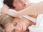 A stock of a couple in bed, the man is snoring and the woman is blocking her ears