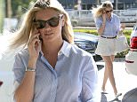 UK CLIENTS MUST CREDIT: AKM-GSI ONLY EXCLUSIVE: Century City, CA - Kate Upton chats on her phone as she visits an office in Century City. The model is wearing white shorts with blue striped button up shirt.  Pictured: Kate Upton Ref: SPL1150958  131015   EXCLUSIVE Picture by: AKM-GSI / Splash News