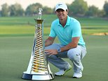 Rory McIlroy of Northern Ireland poses with the European tour championship trophy after the final round of the golf DP World Tour Championship in the Gulf emirates of Dubai on November 23, 2014. The new European number one McIlroy could not win the two trophies he was aiming for, but he said he would have been surprised if he had won the tournament the way he had been playing all week. AFP PHOTO/CHRIS EDRALINCHRIS EDRALINE/AFP/Getty Images