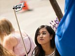 E8MD9G A young woman girl taking a selfie with her iPhone smart phone mobile phone on a short stick pole UK