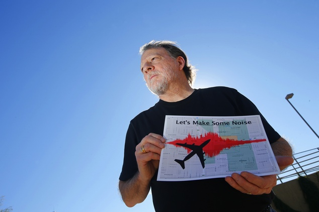 In this Friday, Feb. 6, 2015 photo, Steve Dreiseszun, a resident of the F.Q. Story historic district in Phoenix, holds a graph of the increased noise brought...