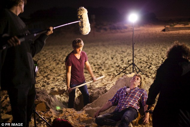 Behind the scenes: An exclusive shot of one of the films harrowing scenes was released showing two of the lead stars near a grave dug by the beach as a film crew surround the actors
