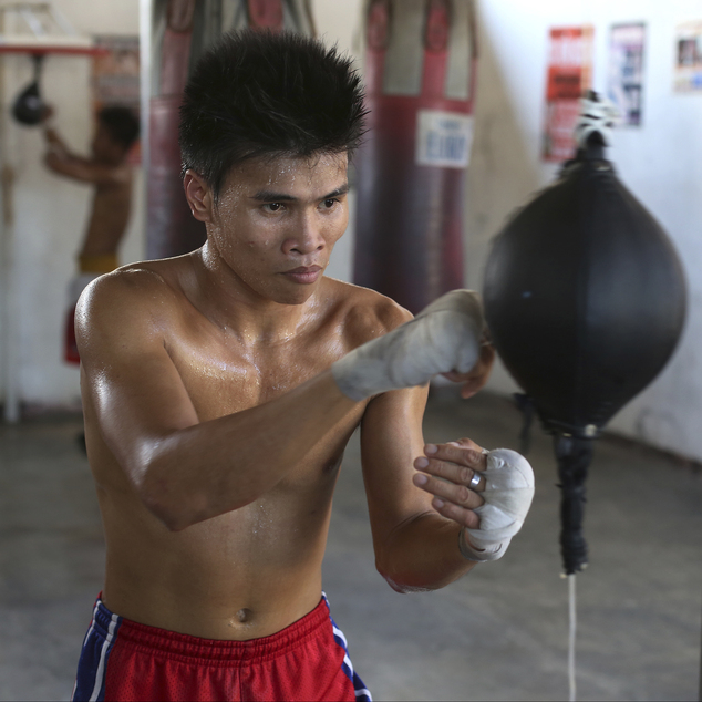 In this April 22, 2015, photo, Filipino boxer Rolly Macaso poses inside a boxing gym in suburban Paranaque, south of Manila, Philippines. Macaso, 21, a forme...