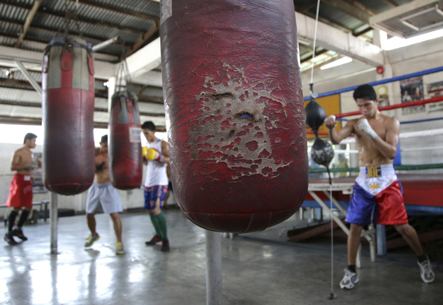 In this April 22, 2015, photo, a worn punching bag hangs at the training area where Filipino boxers practice at a boxing gym in suburban Paranaque, south of ...