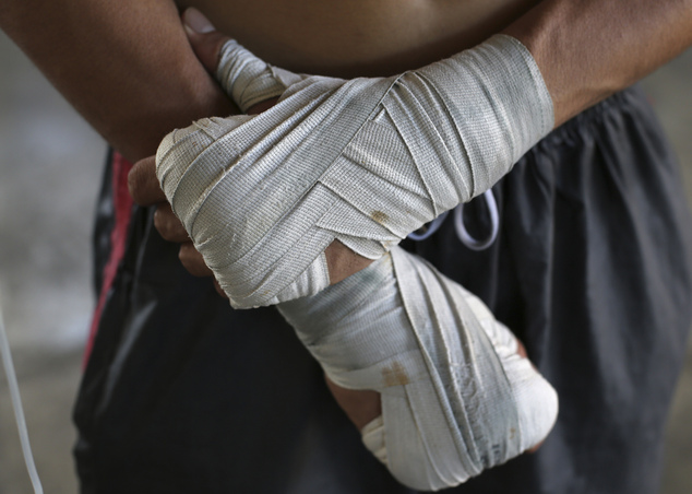 In this April 22, 2015, photo, a Filipino boxer waits for his turn to spar during training at a boxing gym in suburban Paranaque, south of Manila, Philippine...