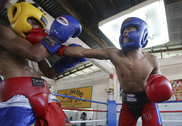 In this April 22, 2015, photo, Filipino boxer Rolly Sumalpong, right, lands a punch on Robert Landero during their training at a boxing gym in suburban Paran...