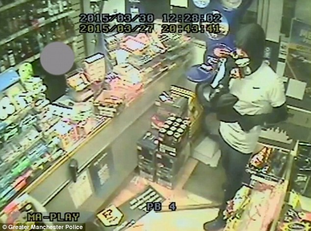 The raiders (pictured entering the premises) robbed the store around 8.30pm on Friday March 27