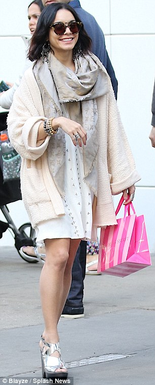 Stylish: She stepped out in style, wearing a plunging white dress with a cream cardigan and silver platforms