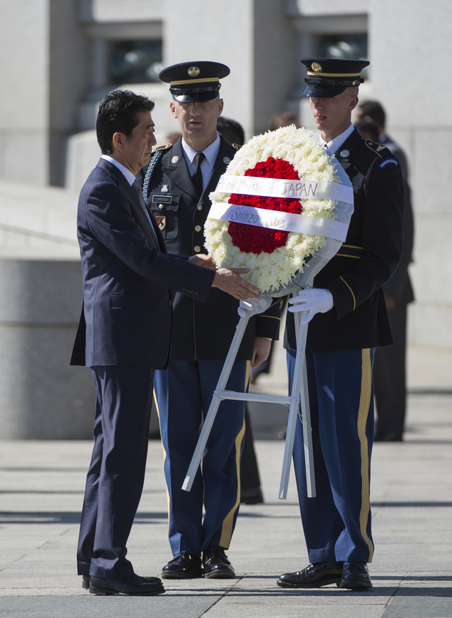 Japanese Prime Minister Shinzo Abe takes part in a wreath laying ceremony at the National World War II Memorial in Washington, Wednesday, April 29, 2015. (AP...