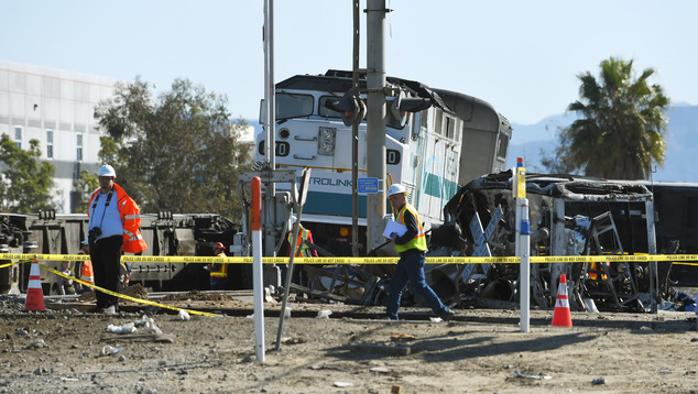 Workers walk near a Metrolink train engine from a train that hit a truck and then derailed on Tuesday in Oxnard, California