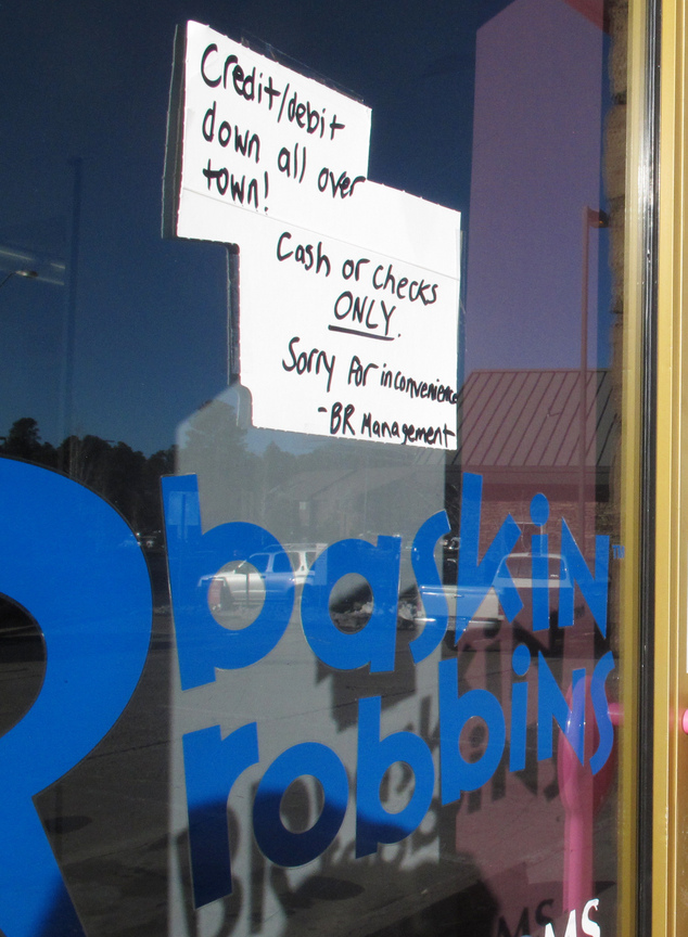 A sign posted outside a Baskin-Robbins ice cream store in Flagstaff, Ariz., Wednesday, Feb. 25, 2015, advises customers that only cash or checks will be acce...