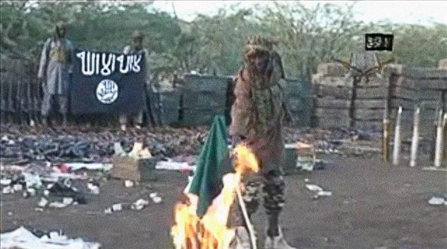 A screen grab made on January 20, 2015 from a video of Nigerian Islamist extremist group Boko Haram shows the group's leader Abubakar Shekau burning a Nigeri...