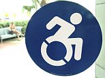 In this Wednesday, Oct. 7, 2015 photo, a modernized handicapped sign is affixed to a door at the The Mall at Millenia in Orlando, Fla. Advocates want to replace the familiar image of a stick figure in a wheelchair with this action-oriented logo to emphasize ability, not disability.  (AP Photo/Bill Sikes)