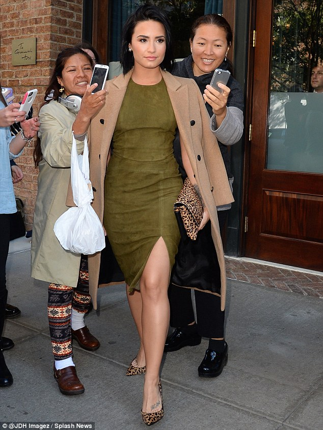 Green goddess: On Thursday, the star donned another curve hugging dress, this time in in a forest green hue, pairing it with a camel colored coat; here she is pictured on Thursday in New York City outside her hotel