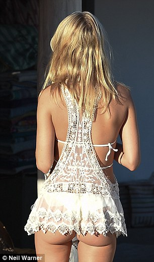 Dare to bare:Browsing numerous stalls after enjoying a lunch date at Club 55, the 25-year-old reality star put on a very cheeky display as she flashed her pert derriere in a sheer white minidress