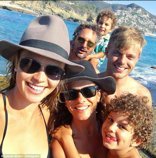Getting some sun: She posed with David and some friends for this photo earlier this week