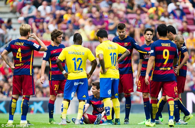 Barca and Las Palmas Players crowd around Messi as the forward sits up before receiving medical help