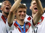 Germany's Thomas Muller celebrates with the World Cup and team-mates Jerome Boateng and Per Mertesacker after the FIFA World Cup Final at the Estadio do Maracana in Rio de Janerio, Brazil.    PRESS ASSOCIATION Photo. Picture date: Sunday July 13, 2014. See PA story SOCCER Final. Photo credit should read: Mike Egerton/PA Wire. RESTRICTIONS: Editorial use only. No commercial use. No use with any unofficial 3rd party logos. No manipulation of images. No video emulation.